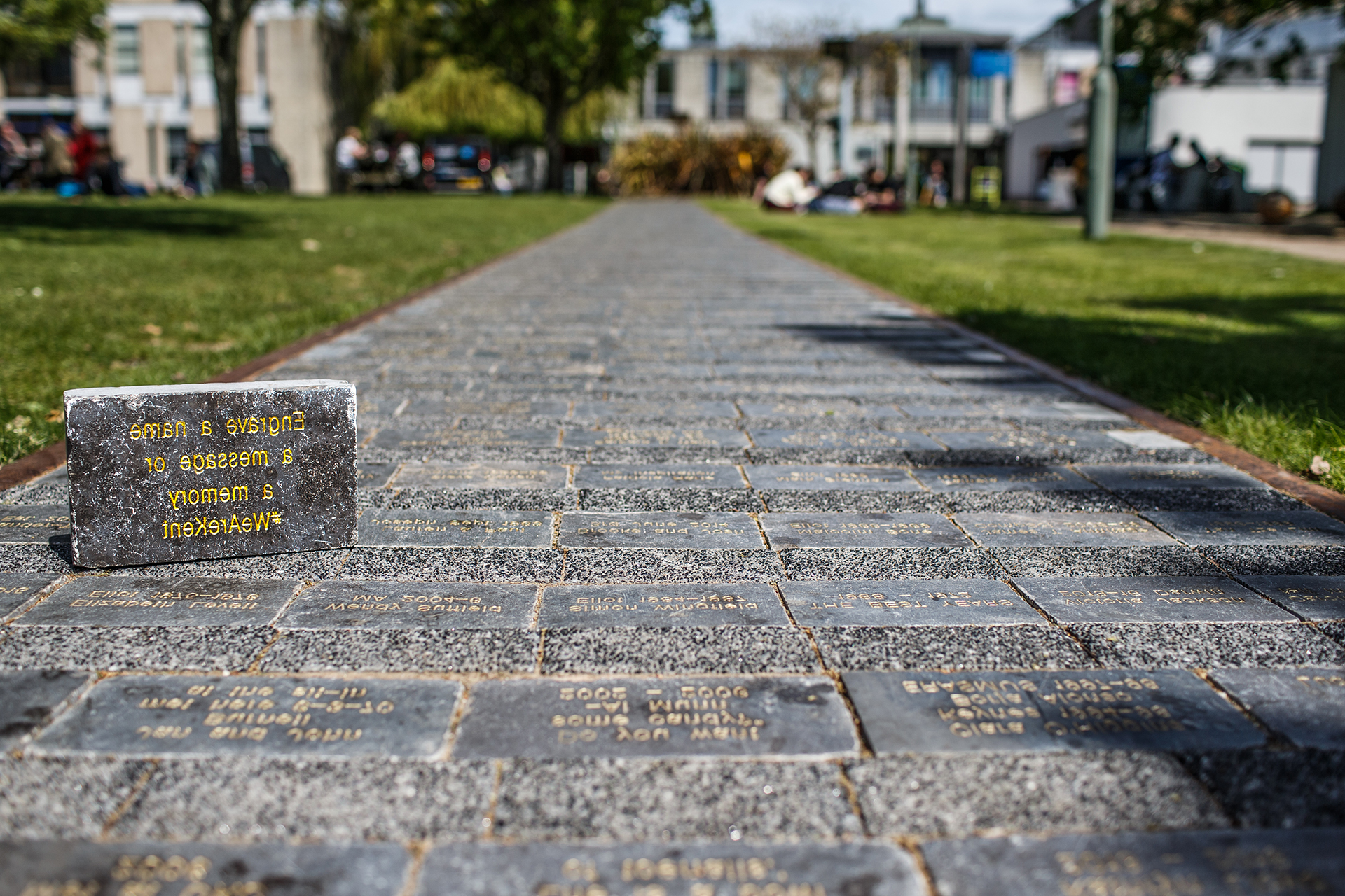 A footsteps brick on the path reading 'Engrave a name a message or a memory #WeAreKent'